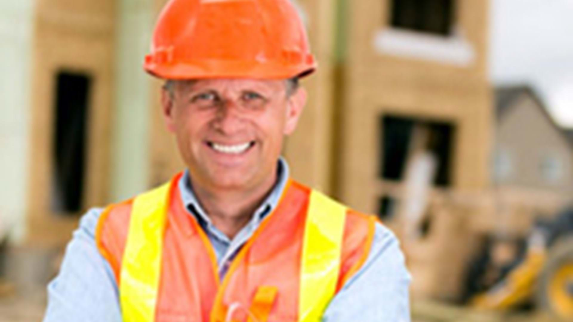 A smiling man wearing a hard hat and a high-vis vest.