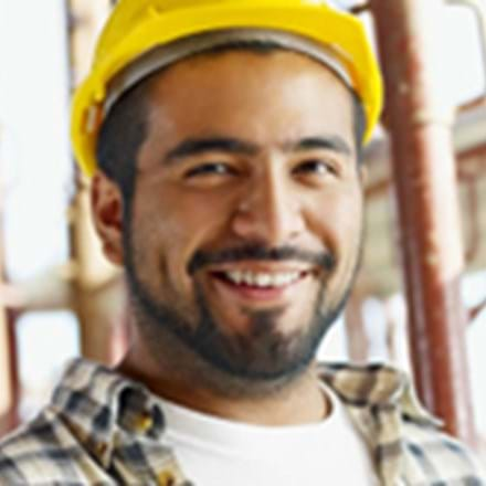 A smiling man wearing a hard hat.